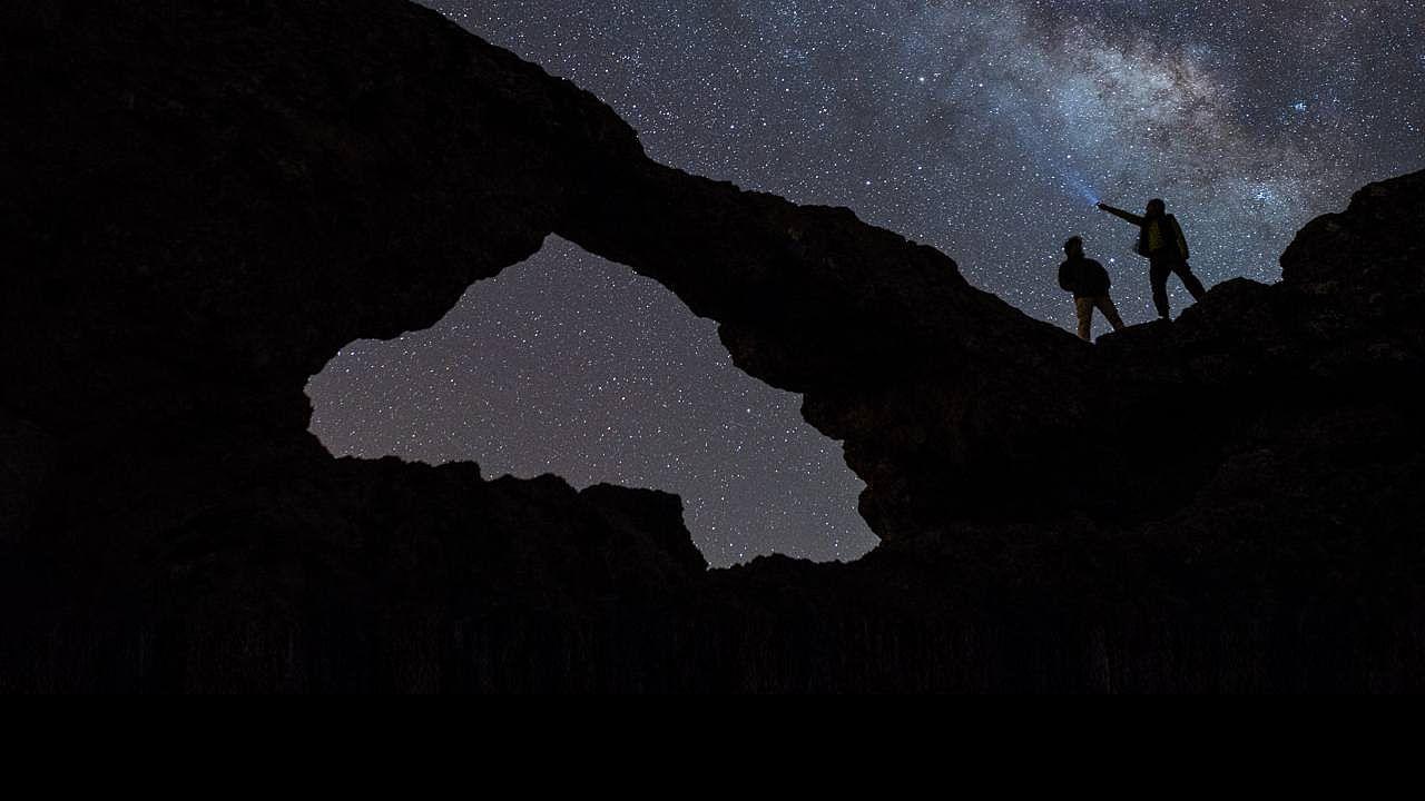Dos personas observan las estrellas desde la Ventana de Pargana en Gran Canaria