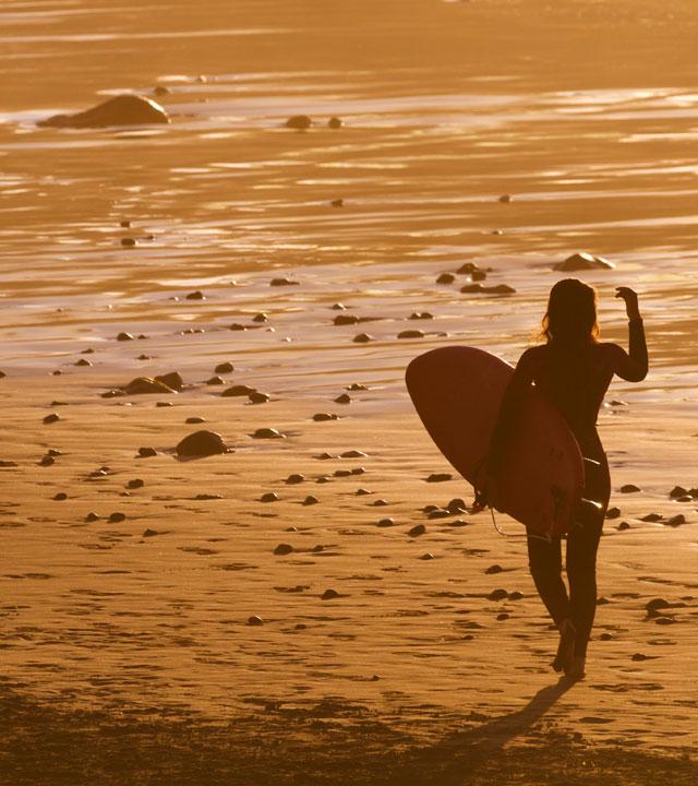 Chica camina por la orilla de la playa con su tabla de surf bajo el brazo
