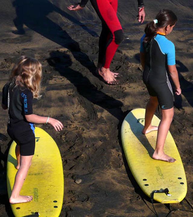 Niños aprendiendo a practicar surf en sus tablas sobre la arena