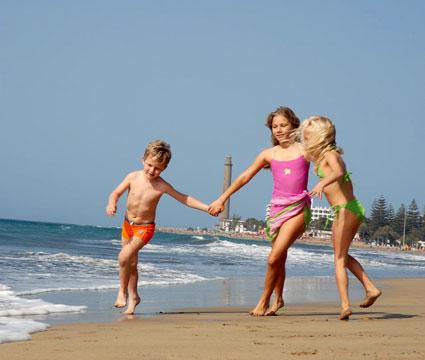 Tres niños juegan en la orilla de la playa de Maspalomas