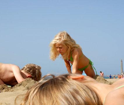 Tres niños juegan en la arena la playa de Maspalomas