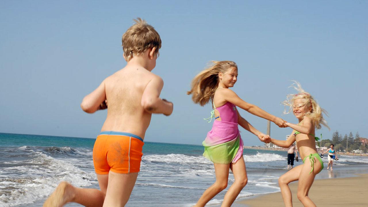 Tres niños juegan en la playa de Maspalomas