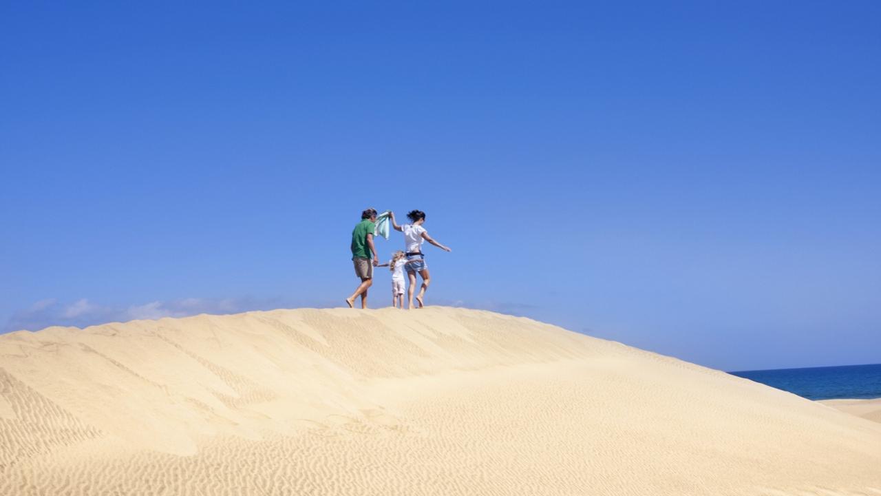 Una familia pasea por las Dunas de Maspalomas