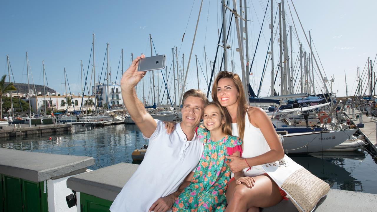 Una familia se hace un selfie en el Puerto de Mogán