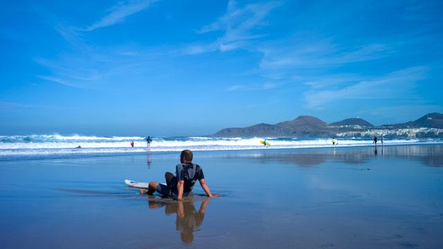 Un surfero descansa en la orilla de La Cícer en la Playa de Las Canteras, Gran Canaria