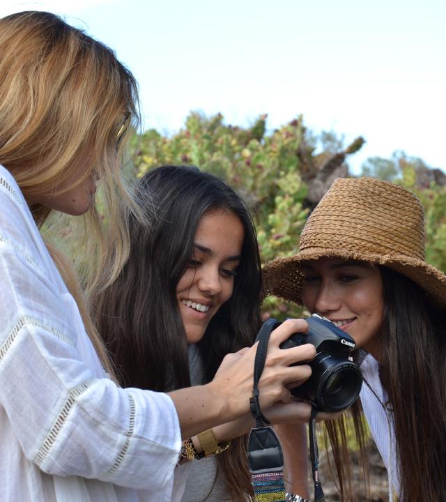 Tres chicas miran en su cámara las fotografías que se han hecho en Gran Canaria