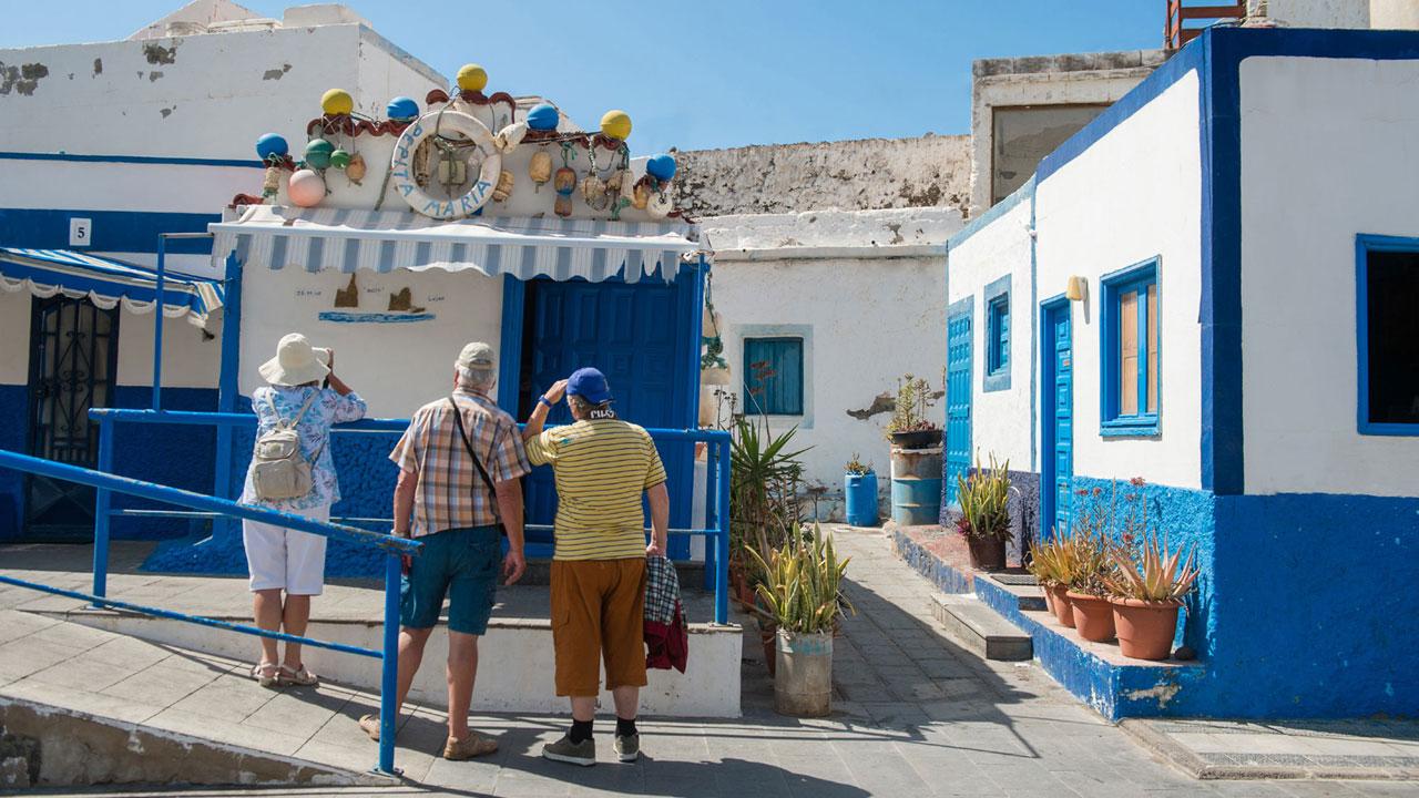 Eine Gruppe von Besuchern beobachtet und photographiert die kleine weiss und blau Häuser von Agaete, Gran Canaria