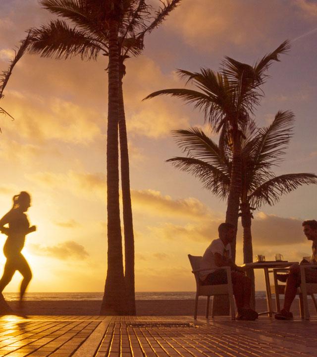 Una chica corre por la avenida de Las Canteras, mientras otras personas toman algo en una de las terrazas