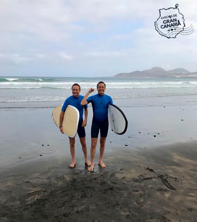 Los cocineros y Hermanos Torres salen del agua con las tablas de surf bajo el brazo en La Cícer en la Playa de Las Canteras