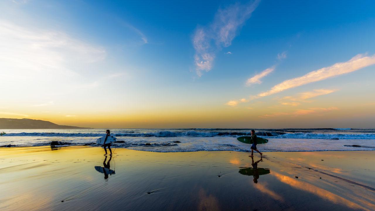 Surferos caminan por la orilla de la Playa de Las Canteras con sus tablas bajo el brazo, al atardecer