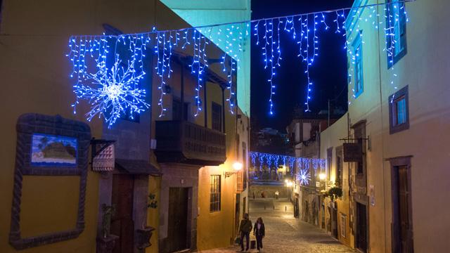 Una pareja pasea por una calle de Vegueta iluminada en Navidad