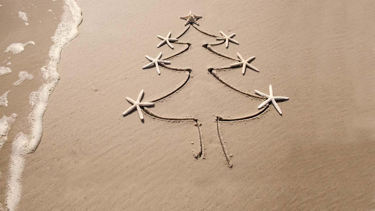Árbol de Navidad dibujado en arena de playa