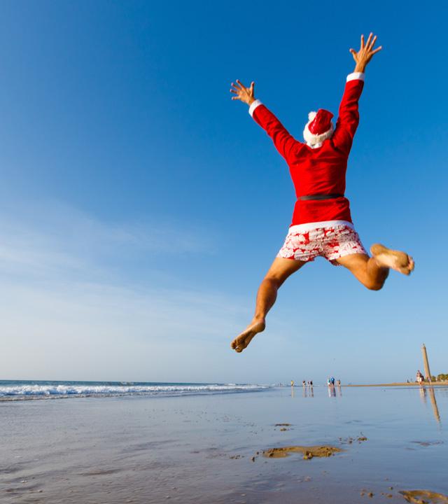Un chico disfrazado de Papá Noel salta de alegría en Maspalomas, en la isla de Gran Canaria