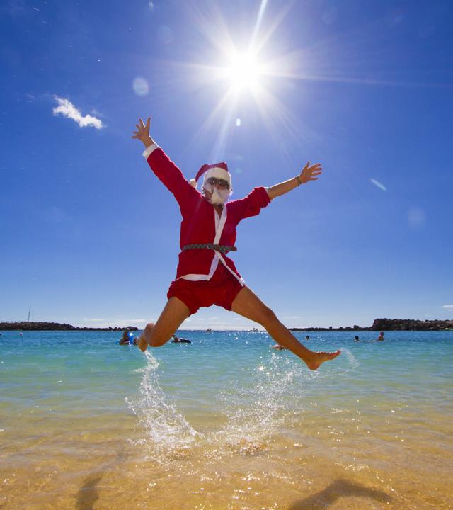 Un chico disfrazado de Papá Noel salta de alegría en la playa de Amadores en Mogán