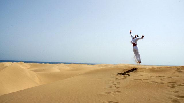 Chico salta mirando al sol, en las Dunas de Maspalomas