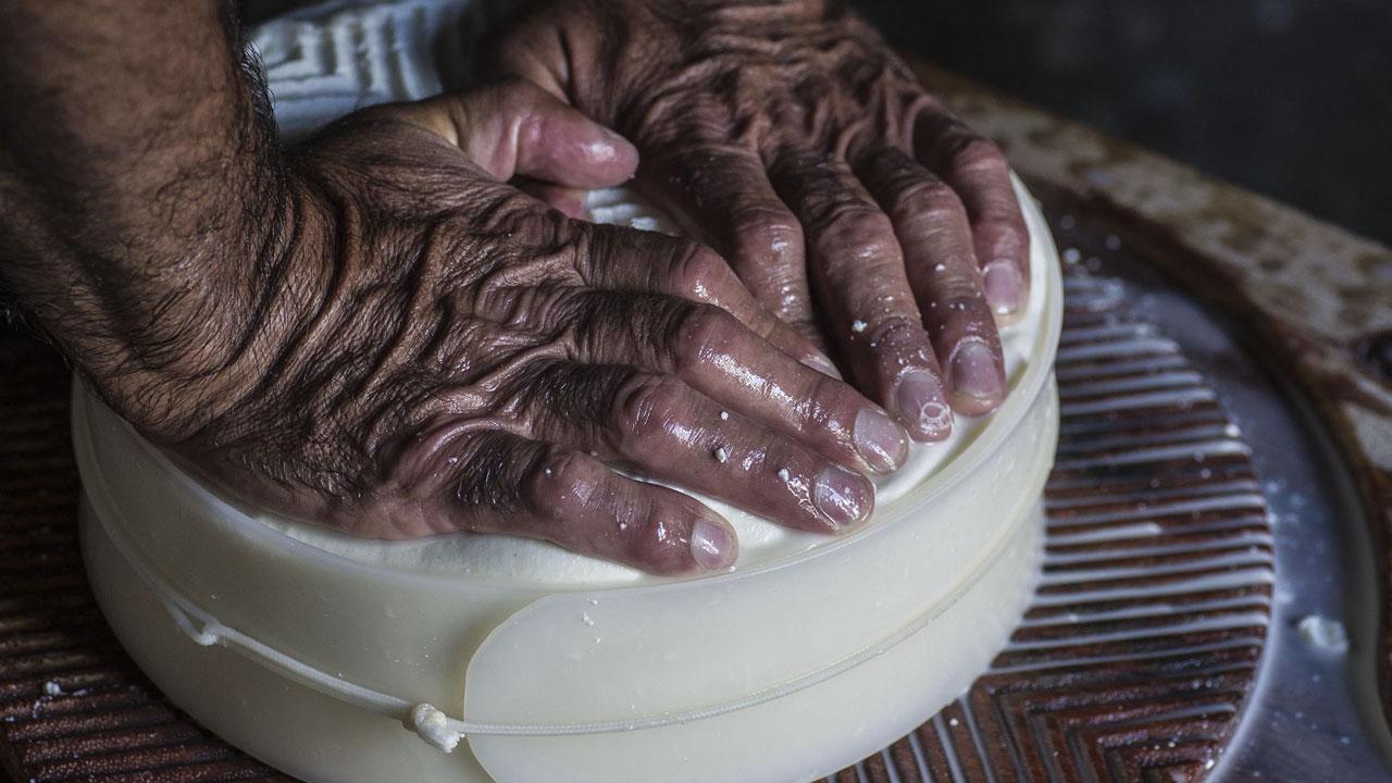 Manos de un señor haciendo queso