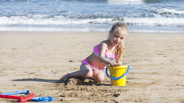 Una niña juega en la arena con su cubo en la playa de Maspalomas, Gran Canaria