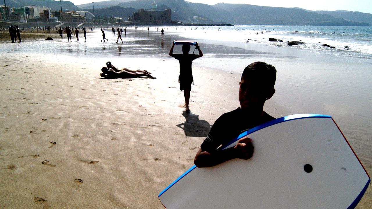 Niño en la playa con su tabla de bodyboard