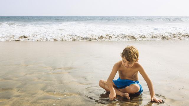 Un niño juega en la arena de la orilla de la playa de Maspalomas, Gran Canaria