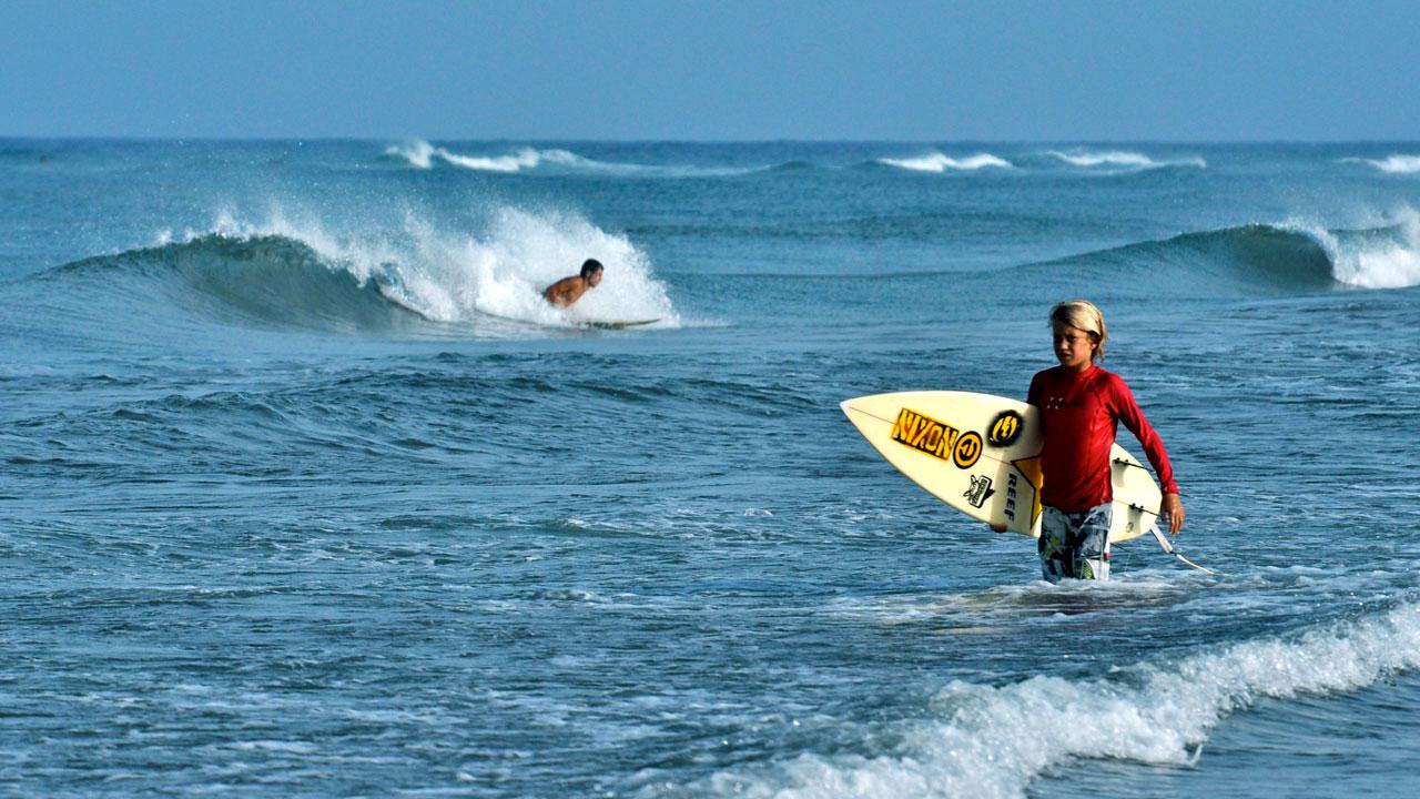 Niño con tabla de surf bajo el brazo, camina por la orilla
