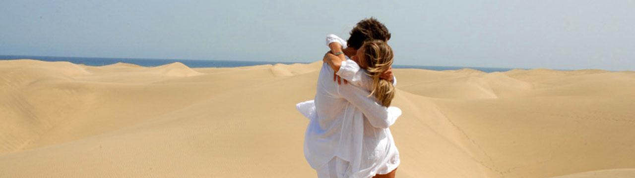 Una chica y un chico se abraza en las Dunas de Maspalomas