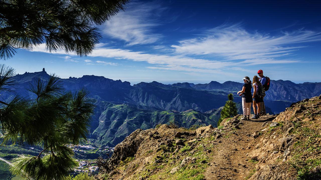 Tres personas contemplan las vistas del Roque Nublo, al fondo de la imagen