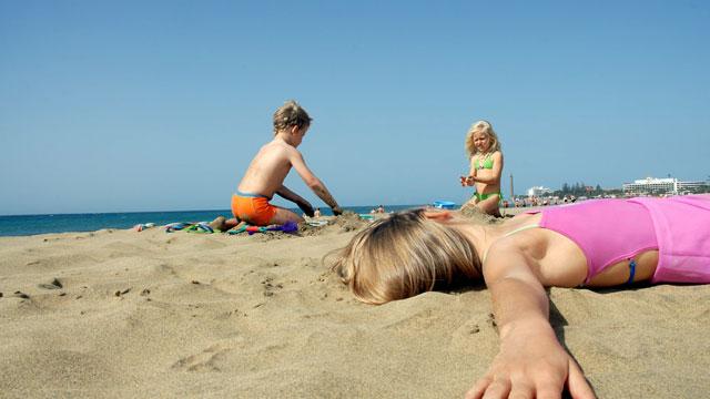 Tres niños juegan en la arena de la playa de Maspalomas