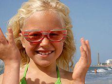 Flicka med färgade glasögon ler på stranden i Maspalomas med fyren som fond