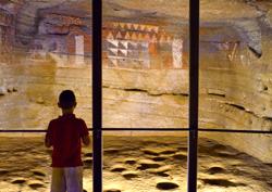 Un niño frente a las pinturas aborígenes de la Cueva Pintada