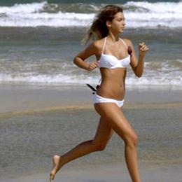 Una niña corren por la orilla de Playa del Inglés