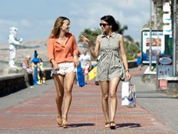Dos jóvenes charlan animadamente por el paseo de Meloneras