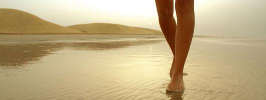 Girl strolling along the shore on Maspalomas beach