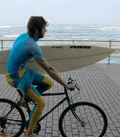 Surfista a passear de bicicleta por Las Canteras