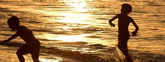 Bambini giocano sulla spiaggia di Las Canteras al tramonto