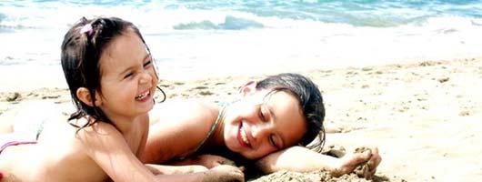 Skrattande flickor leker på Canterasstranden
