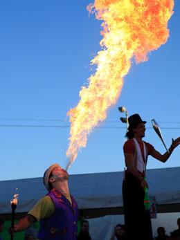 A fire-eater shoots a flame high up into a deep blue sky