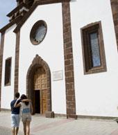 Una coppia passeggia davanti alla Chiesa di Artenara