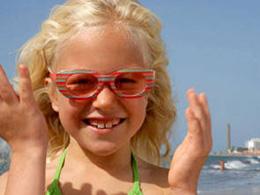 Lachendes Mädchen mit bunter Brille am Strand von Maspalomas, im Hintergrund der Leuchtturm
