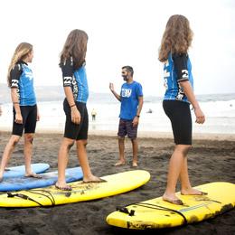 Un groupe de filles écoute attentivement les instructions du moniteur sur la plage