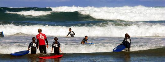 Rapazes com o monitor a surfarem com as suas pranchas à beira-mar