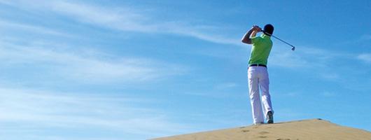 Um golfista sobre uma duna sob o céu azul