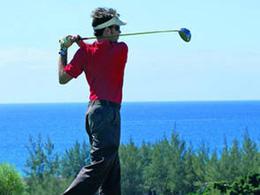 Un golfeur tente le coup de sortie avec la mer en fond