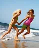 Zwei Mädchen laufen am Strand von Maspalomas durch die Wellen
