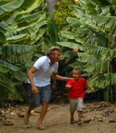 Vater und Sohn spielen in der Bananenplantage Verstecken