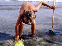 Un niño se prepara para entrar al mar en Sardina