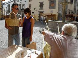 Un couple achète un panier en osier sur le marché de Vegueta