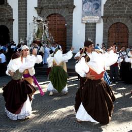 Gruppo di persone con i costumi tradizionali ballano durante le Feste del Pino