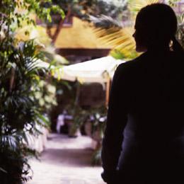 Una chica observa el interior de un patio canario en Vegueta